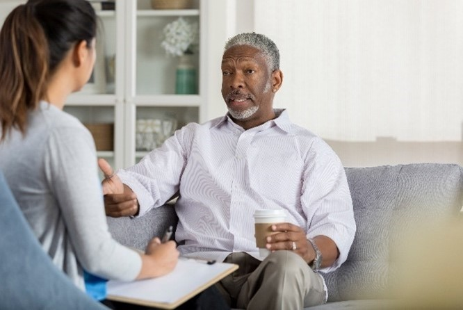 Elderly black man in counselling, sitting on a coach and talking to a woman who has their back to the camera.
